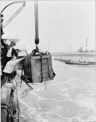 Harry Houdini, being lowered from ship