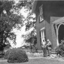 Unknown #25 - Two men in front of a house