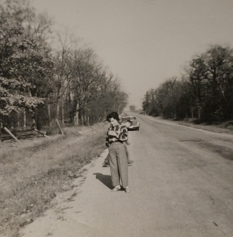 Pearl Stawnychka picked an apple from the many apple orchards along the mountain brow. Photo taken in Hamilton ON in the 1950s.