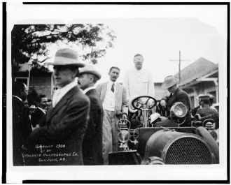 [President Theodore Roosevelt, standing in automobile, at...