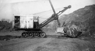 Clearing a boulder with a steam shovel
