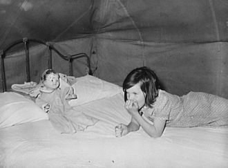 Child migrant with doll in tent home. Harlingen, Texas
