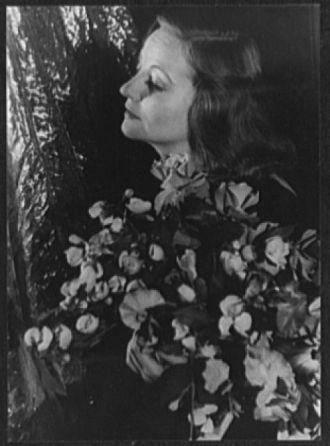 [Portrait of Tallulah Bankhead holding floral bouquet...