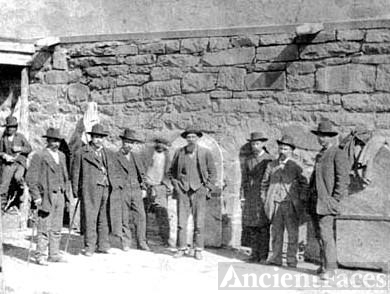 Photo taken in front of the Old Town Jail in Las Vegas, New Mexico. John Joshua Webb is shown here, with his feet shackled, in the center of the photo.