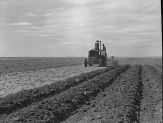 Dust bowl farmer driving tractor with young son near...