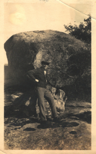 Man in front of a large rock