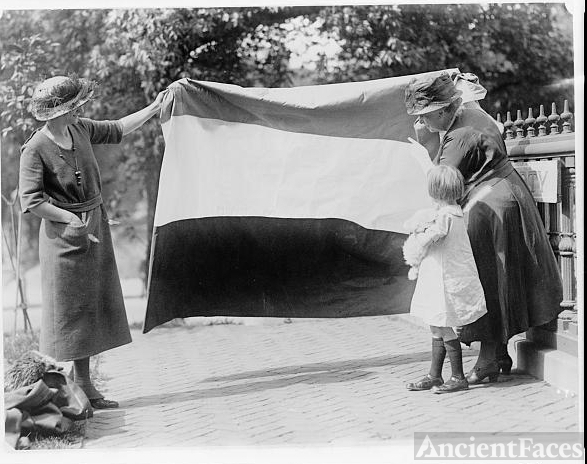 Two suffragettes showing banner to young girl