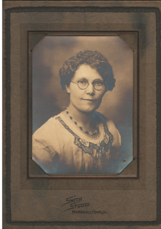 Woman with short curly hair and glasses
