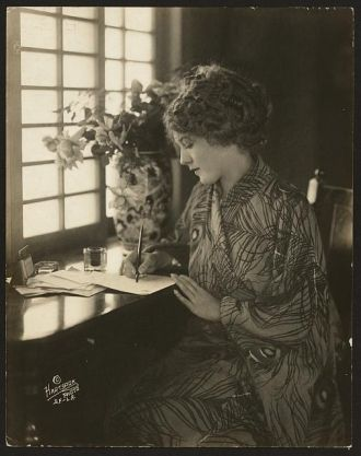 [Mary Pickford, wearing a kimono, writing at a desk] /...