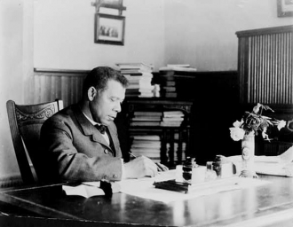 [Booker T. Washington, half-length portrait, seated at...